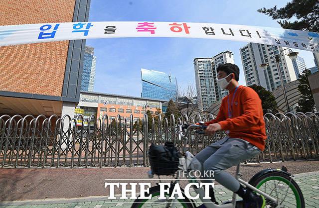 코로나19 여파로 전국 유치원·초중고 개학이 1주일 연기된 지난달 24일 오후 한 시민이 서울 마포구의 한 중학교 교문사이로 지나가고 있다./이동률 기자