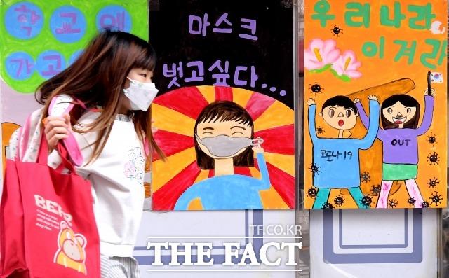 교육부가 오는 19일부터 대부분 시·도교육청이 학교생활 적응을 이유로 초등학교 1학년을 매일 등교시키기로 했다.서울 마포구 동교초등학교 인근 거리에서 어린이가 코로나 관련 그림을 바라보며 걸어가고 있다. /이선화 기자