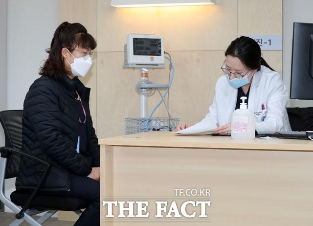 27일 오전 서울시 중구 을지로 국립중앙의료원 중앙예방접종센터에서 화이자 1호 접종자인 의료원 관계자가 백신을 접종에 앞서 예진을 받고 있다. /사진공동취재단
