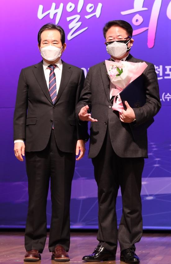 조정현(사진 오른쪽)은 3일 오후 서울 중구 대한상공회의소에서 열린 제10기 국민추천포상 수여식에서 정세균 국무총리로부터 직접 훈장을 받았다. /정현웨딩 제공