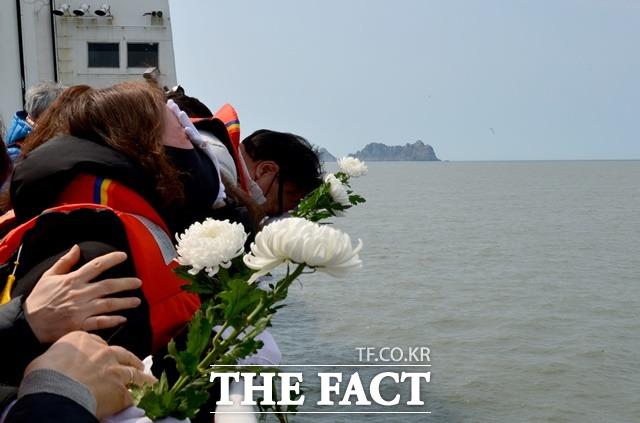 세월호 참사 7주기인 4월 16일 오전 희생자 가족들이 전남 진도군 동거차도 인근 사고 해역을 찾아 바다를 향해 국화를 던지고 있다./뉴시스