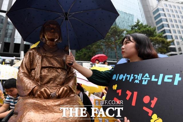 '국가면제' 이론에 막혀 각하 판결이 나왔던 일본군 위안부 피해자의 손해배상 소송 항소심 선고가 내년 5월로 내려진다.. 사진은 2019년 7월 1397차 일본군 성노예제 문제 해결을 위한 정기 수요집회가 24일 오후 서울 종로구 옛 일본대사관 앞에서 열린 가운데 한 참가자가 소녀상에게 우산을 씌워주고 있는 모습. /남용희 기자